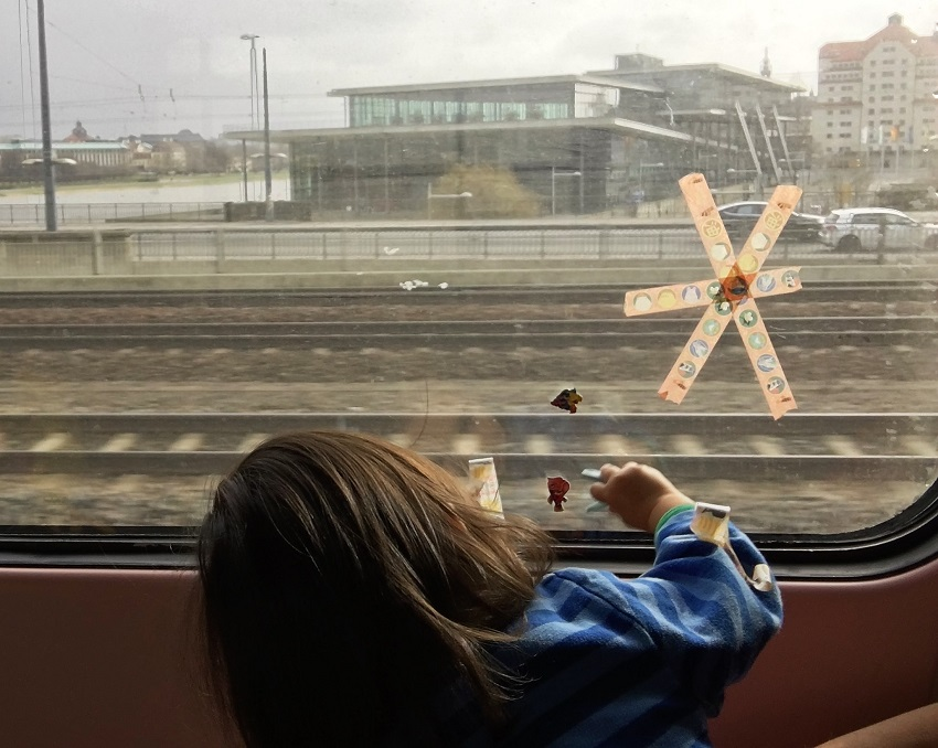 Playing with stickers on a train window